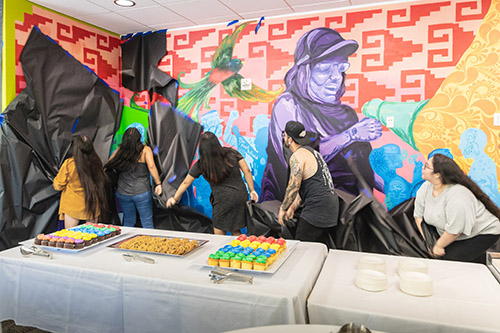 Students unveiled a mural that represents the university's past, present and future at the opening ceremony for the Multicultural Center.